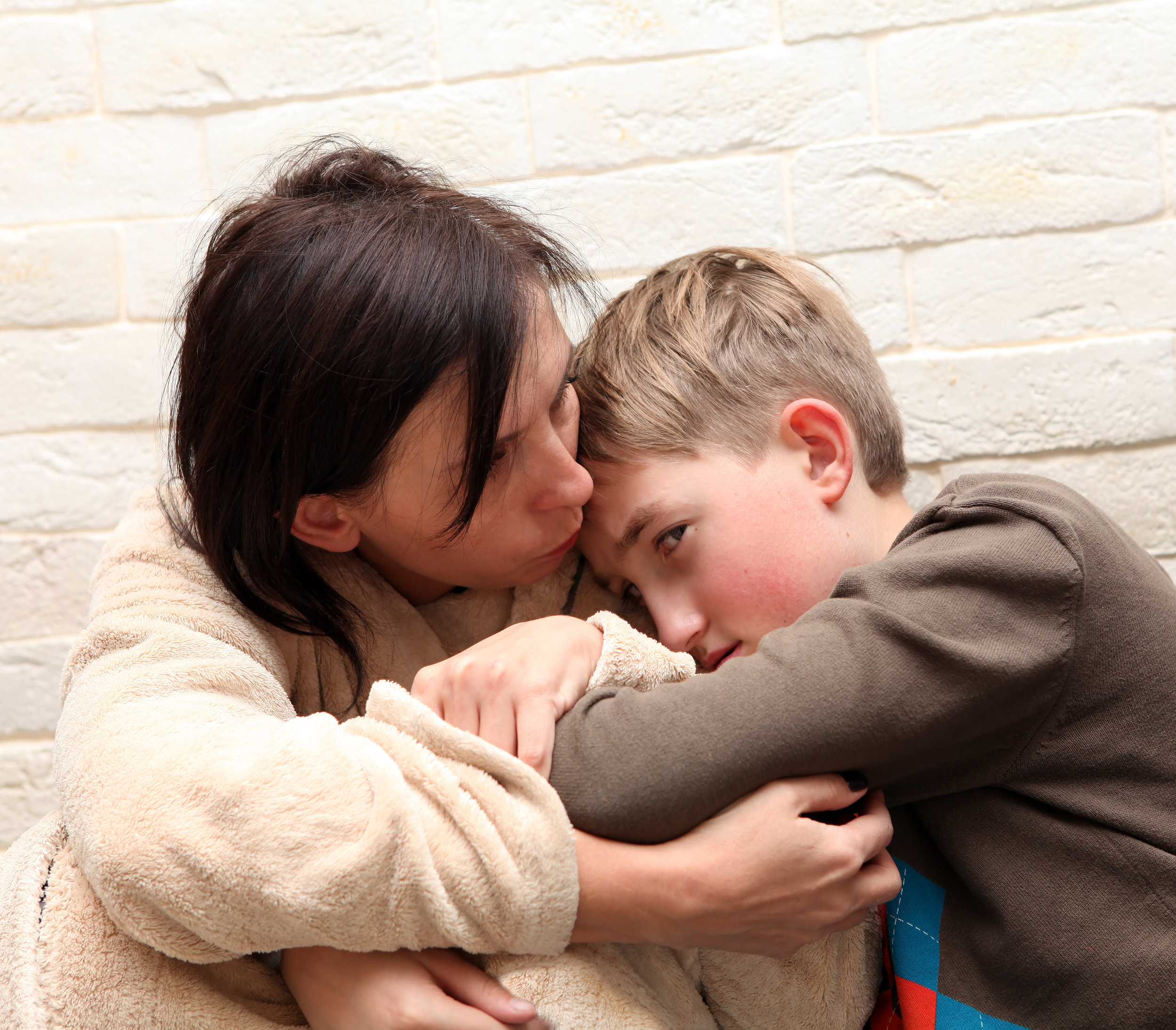 child being comforted by woman